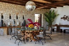 On the dining terrace of a home in Ibiza, a 1970s mirrored ball sparkles above a sculptural table surrounded by metal chairs from Morocco; the seat cushions are covered in a Pierre Frey linen.