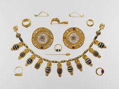 Set of Etruscan jewelry, early 5th C. B.C. (Late Archaic Period). Said to be part of a tomb group from Vulci. Gold and glass necklace; gold and rock crystal disks; two plain gold fibulae (safety pins); gold fibula with sphinx; gold straight pin; gold and agate ring w/ scarab & a youth on bezel; gold and carnelian ring w/ scarab & Herakles on bezel; gold and carnelian ring w/ bird on bezel; gold ring w/ lion on bezel; plain gold ring.