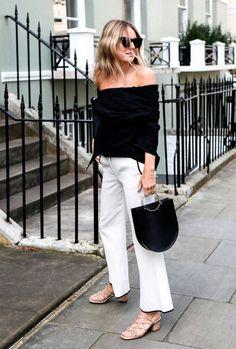 Street style look calca cropped branca, sandália bege e blusa ombro a ombro preta.