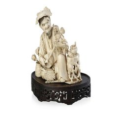 A Japanese ivory carving of a kneeling musician playing a shamisen, Meiji Period, with a toad on his shoulder, a tree trunk with urn and scroll, and a vase of flowers by his side 16 cm high
