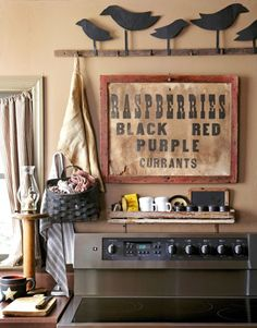 """Just love the look of them up on the wall - In this primitive home's kitchen, a frieze of folk-art tin crows watches over a fruit sign found in southern Indiana and an unabashedly """"modern"""" Kenmore Elite stove. Primitive Homes, Primitive Kitchen, Country Primitive, Primitive Decor, Primitive Bedroom, Primitive Signs, Prim Decor, Country Farmhouse Decor, Farmhouse Style Decorating"""