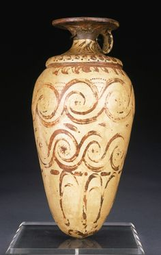 A MINOAN POTTERY RHYTON   late minoan ib, circa 1500-1450 b.c.   The ovoid vessel with a tapering body, rounded base, ridged shoulder, and waisted neck, with a ring handle below the disk rim, the base perforated, decorated with two large bands of spirals above petals rising from a central rosette on the base, bands of comma-shaped motifs on the shoulders and neck  9½ in. (24.1 cm) high styl  pałacowy