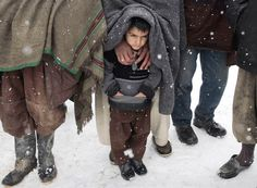 A child stands with his father as they wait to receive blankets and winter jackets from a German aid organization at a camp for internally displaced Afghans in Kabul, Feb, 20. More than 40 people, most of them children, have frozen to death in what has been Afghanistan's coldest winter in years.