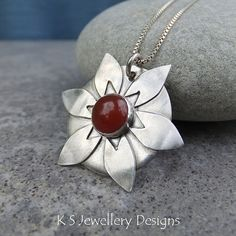 This flower pendant features a deep orange carnelian cabochon set on a sterling silver disc surrounded by six petals cut out from sterling silver sheet. To highlight the details, I have lightly oxidised the whole piece.