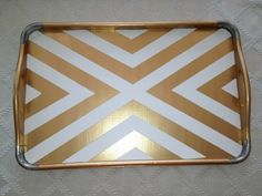 Use painter's tape and gold spray paint to create a sophisticated and glamorous pattern on a tray.