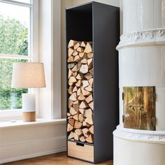 The wood storage stand has a stable frame of heavy black HPL and provides sufficient depth for logs. In the wood box in the base there is practical storage place for paper and firelighters. Fireplace Hearth Tiles, Brick Hearth, Brick Fireplace Makeover, Modern Fireplace, Indoor Log Storage, Indoor Firewood Rack, Firewood Stand, Wood Burning Logs, Freestanding Fireplace