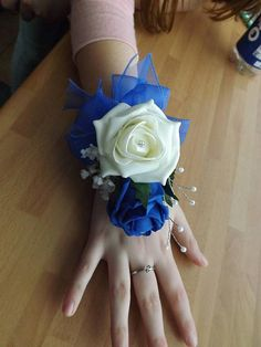 Here we have a beautiful wrist corsage made with ivory and royal blue foam roses, trimmed with diamante, sprays of pearls and gypsophillia then finished with a royal blue organza bow and ribbon tie.