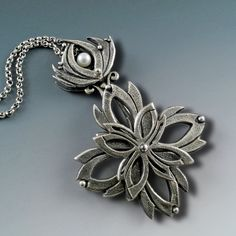Kinetic Lotus Flower by Holly Gage. Beautiful sub-patterns appear while the center petals spin. Hand sculpted in fine silver metal clay with 5 mm pear. 67 mm x 45mm.