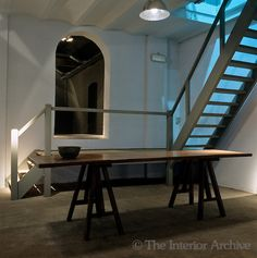 A bowl stands at one end of a polished trestle table in this industrial space