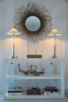 A light composition of faves/collectables on white shelving topped with 2 slim buffet lamps with a bronzed sun burst mirror.....creatively subtle.
