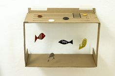 Wall Hanging Box Aquarium - It's actually really beautiful to watch.  When you slide the buttons, the fish spin and dance, creating a happy swimming effect.  It's a great recyclable toy.  You could leave the back and sides of the box attached.    It would be fun to paint the inside of the box too though.  Try it out!