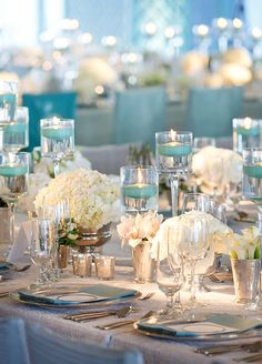 Colored floating candles make dramatic effect! <3 Shop now at www.YummiCandles.com  White flowers interspersed with floating tiffany blue votive candles in varying heights. You don't want to miss any details of this Modern Classic Miami Wedding created by the Colin Cowie team.