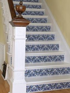 This old staircase was in desperate need of an overhaul. To get the job done, the old rubber mats were pulled up and the surface of the entire staircase was smoothed out, primed and then painted.  Then, to give the staircase a bold pop of personality, wallpaper that resembles tile was adhered to the risers.