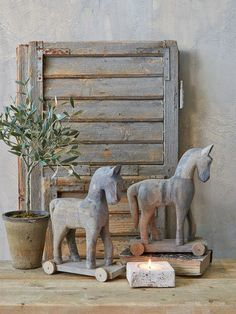 Vintage shutter and rocking horses in display.