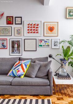 Sofá cinza, luminária jieldé, quadros de artistas diversos e almofada geométrica da marimekko.