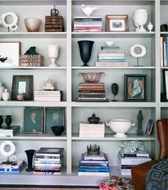 Analysis of a Well Styled Bookcase.Varied groupings of three or five are always visually appealing.balance achieved between the books alternating in placement from left to right with the ceramics poised on the opposite side. The middle shelf repeats the books plus ceramics combination, and also provides the opportunity to display smaller collectibles. Different heights and textures also add to the appeal.