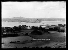 1910? Looking north from near the foot of Mangere Mountain across the Manukau Harbour towards One Tree Hill and Onehunga (centre background) showing Mangere Bridge, Ohehunga Wharves and Onehunga Beach (centre left). Sir George Grey Special Collections, Auckland Libraries, 35-R235.