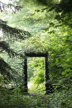 Bäume und Rankpflanzen als Türrahmen machen den Garten märchenhaft.