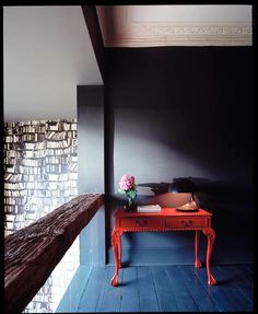 A black hallway with a red console table and single flower