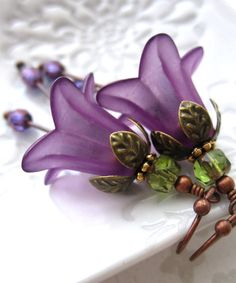 Romantic, rich, purple flower earrings. Smooth, velvety, matte acrylic flowers are topped with antiqued copper leaf caps and earthy green fire-polished