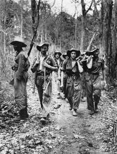 A group of tired Chindits bring out a stretcher case towards the photographer, immediately behind whom is the light jungle airstrip. The man at left carries two Enfield rifles, the other being the wounded man's. To his right is a Black West African Chindit who watches the jungle for Japanese raiders. The men were from First Platoon, 41 Column, 2nd King's own Royal Regiment