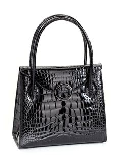 The Thompson Grommet Tote. The grommet, inspired from an industrial concept, is elevated by exquisite jeweled inlay and exotic trimmed detailing. Magnetic closure, zipper pocket, two eyeglass/cell poc
