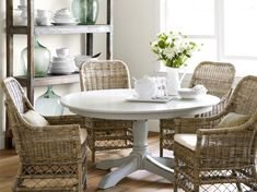 """Dining Room Instead of color, textureâ€""""wicker chairs, an aged wood shelving unitâ€""""provides interest. Fresh flowers and glass bottles add a subtle hit of green."""