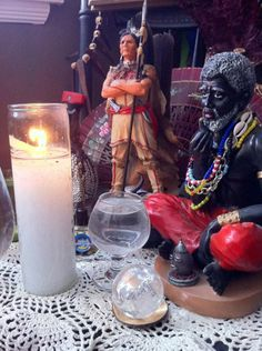 Working with Ancestors (How to) ~ Statues depicting Indian and Congo spirits grace this simple bóveda along with a glass of water, crystal ball and a white candle.