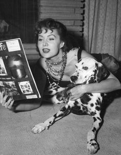 0 Rhonda Fleming reading a book to her dalmatian