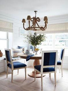 """Toby and Will had a banquette installed during the renovation, a decision they feel """"encourages guests to linger."""" Beneath a rope-wrapped chandelier by Jamie Young, a round pedestal table and color-blocked velvet chairs provide just the right amount of comfort and formality."""