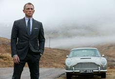 """James Bond (Daniel Craig) and his classic Aston Martin car in Sam Mendes' """"Skyfall.""""   Photo Credit: Sony Pictures"""