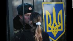 Oleg, a Ukrainian soldier at the Belbek military base, kisses his girlfriend Svetlana through the gates of the base entrance on March 3, 2014 in Lubimovka, Ukraine.