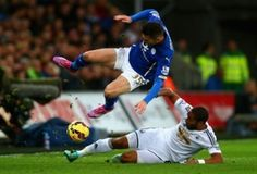 Ashley Williams of Swansea City, with a textbook tackle from the school of no-nonsense football. David Nugent of Leicester City looks like he's in for a heavy landing.