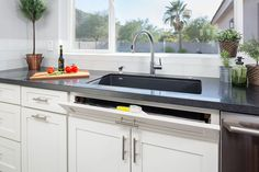 modern kitchen sink wall has large window, white shaker cabinets and sink tip out tray for small item storage and pull-out trash can