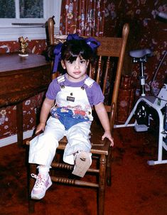 Looking adorable with her hair up in pigtails with purple ribbon, Kim Kardashian posed for picture while wearing a purple t-shirt and white overalls. Click the picture to see more of her childhood photos