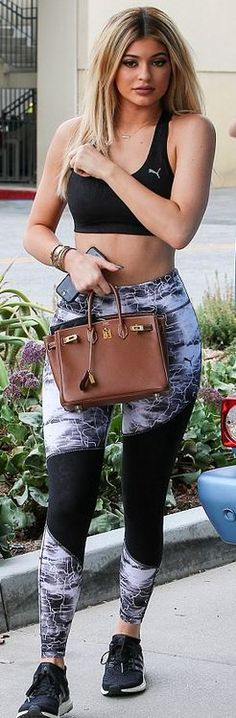 Who made  Kylie Jenner's black sneakers, gold jewelry, top, and gray print leggings?