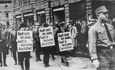 """Three Jewish businessmen are forced to march down a crowded Leipzig street while carrying signs reading: """"Don't buy from Jews. Shop in German businesses!"""" Leipzig, Germany, 1935."""