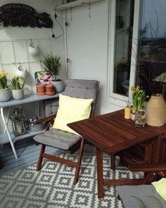 Klappmöbel aus Holz, grauer Teppich und Sitzkissen, gelbe Dekorationen