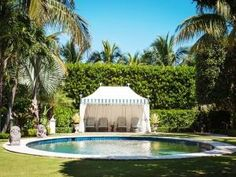 pool with tented cabana and striped chaise lounges // pools by lea