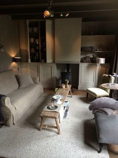 I K I - Stamkamer. Long rustic wooden coffee table surrounded with linen armchairs and sofa.