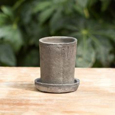 """Using a traditional aging process, these handmade pot and saucer pairs are wrapped in linen, then stowed in a root cellar for several months, where minerals react in the clay to develop a textured, slate finish with pale gray highlights.- Handmade, variation will occur- Clay- Indoor or outdoor use- Drainage hole not included- Can be rinsed to achieve darker slate tone- Imported5""""H, 4"""" diameter"""