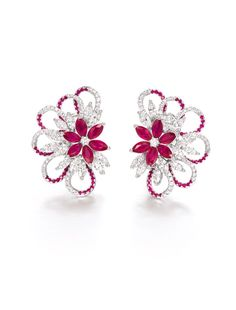 RUBY AND DIAMOND EAR CLIPS. Of floral design, each set with clusters of marquise-shaped rubies and diamonds, to a swirl set by circular-cut rubies and diamonds. Rubies and diamonds together weighing approximately 4.30 and 3.40 carats respectively. Mounted in 18 karat white gold.