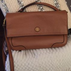 Tory Burch Foldover Crossbody Authentic Tory Burch fold over crossbody bag in beautiful luggage color. In pristine condition. I love, love, love this bag! It also has an adjustable crossbody strap that can also be removed to use as a large clutch. How perfect is that ?! Large and hard to find ! Hence the price Tory Burch Bags Crossbody Bags