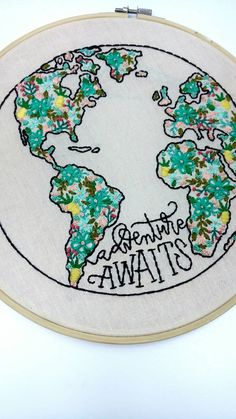 Original ten inch embroidery hoop art. This unique, original fiber art piece features an original free-handed globe illustration, filled in with delicate floral accents and accompanied with the travel inspired quote, Adventure Awaits.  Your piece comes fully backed and finished, ready to hang or display any way you wish! Please note that every piece is an original and done by hand, so there may be slight variations from the picture.  ITEM DETAILS -One ten inch hoop art piece -Custom original…