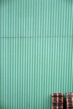Photography ideas and inspiration. Old pallets stacked against a mint green factory wall. I love this image and composition. Photographer unknown.