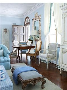 White Gustavian chair in the mix with other antique pieces in a sitting area with a mix of light and bright blues