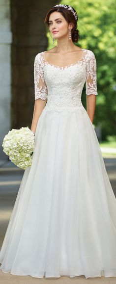 This organza full A-line gown features illusion lace three-quarter length sleeves and scoop neckline, sweetheart lace bodice with a scalloped natural waist.
