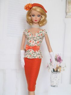 Barbie wearing a stunning orange outfit and matching hat!