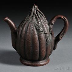 Yixing Teapot with Warmer on Base, China, 20th century, in the shape of a Buddha's hand citron resting on a waisted foot, the handle in the shape of a sprig with gnarls and leaves, incised surface details, a mark to the bottom of the handle, ht. 5 1/2 in.