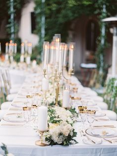 gold rim glassware and gold border glass charger plates pop on these white linens, paired with full and lush floral garland for table centrepieces with gold candelabras | European Inspired California Estate Wedding